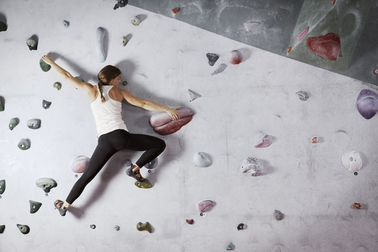 Female climber scaling climbing wall