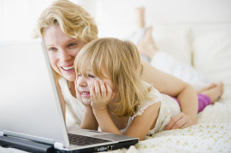 Mother and daughter using laptop together in bed