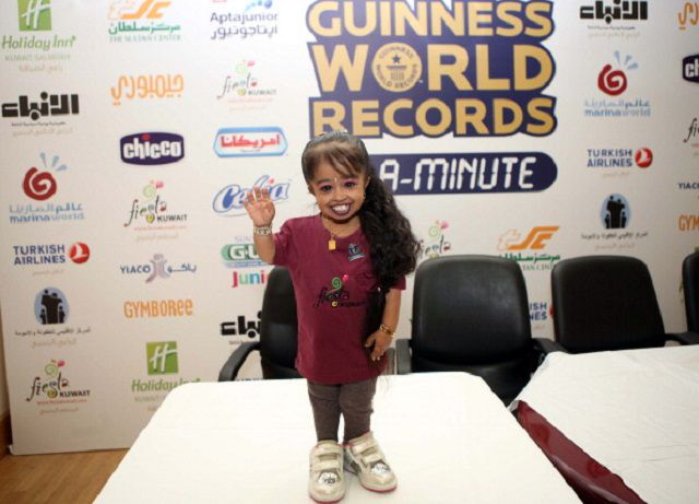 Jyoti Amge, 19, the world's shortest woman according to the Guinness Book of Records, poses for pictures during an event in Kuwait City, on March 14, 2013.