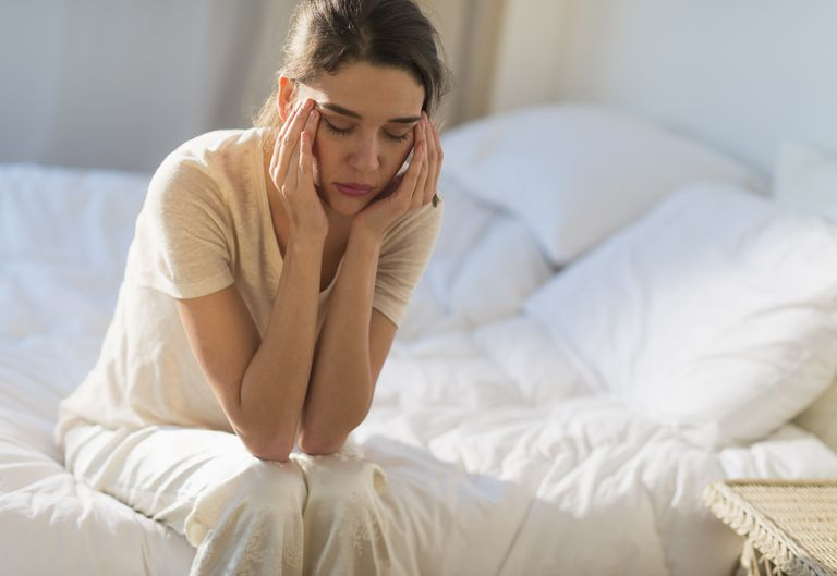 Young woman sitting on bed with headache