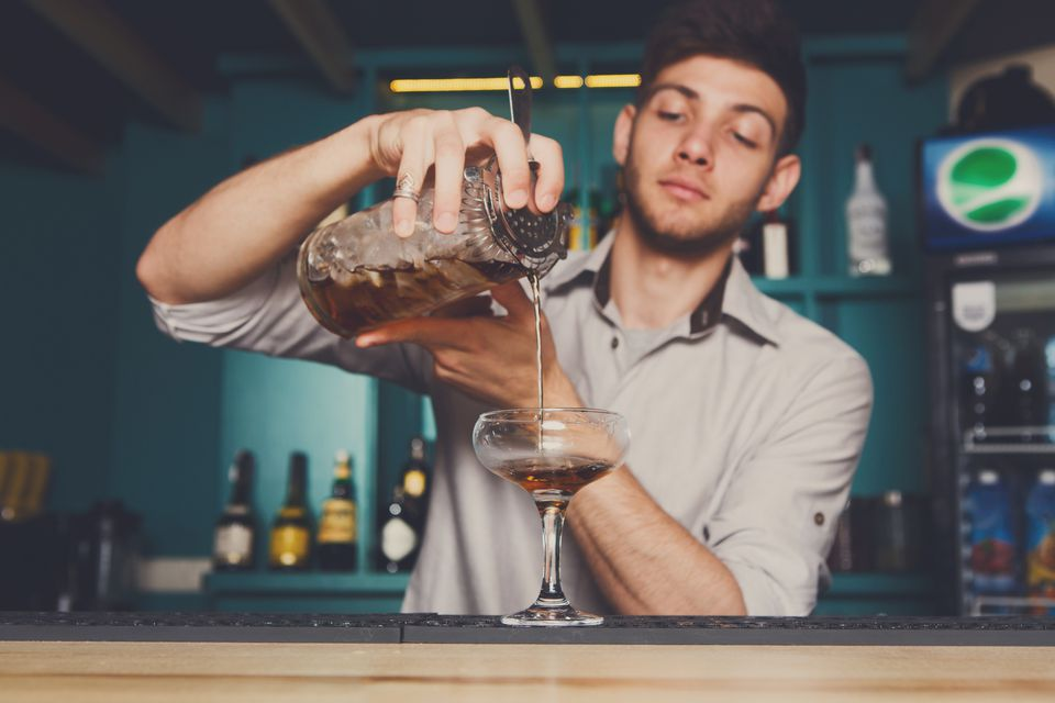 Young male bartender straining a cocktail into a champagne coupe.