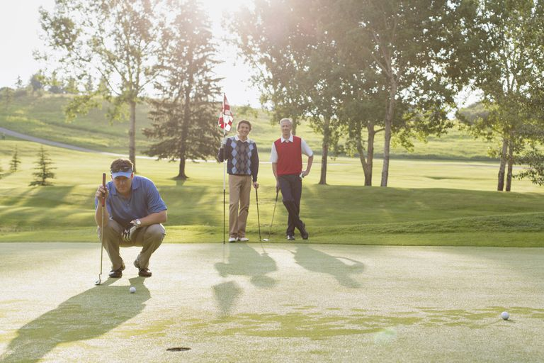 Threesomes match with three golfers on a putting green