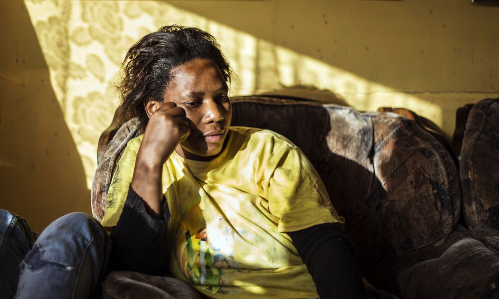 Upset African American woman sitting on couch at home