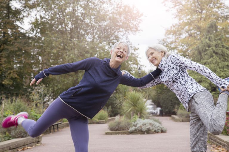 two elderly women stretch in street before exercising