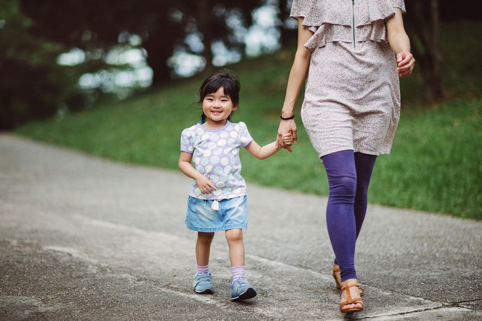 Little girl strolling in park with mom joyfully