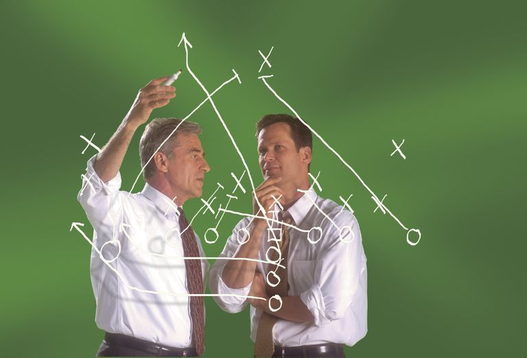 Businessmen discussing diagram of a football play
