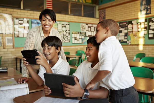 Teacher and students looking at tablet