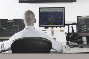 Computer systems analyst looking at monitors