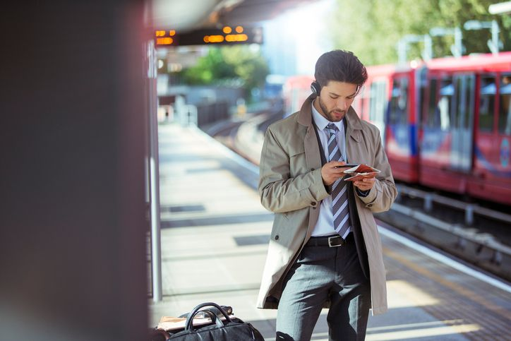 Businessman using cell phone in train station