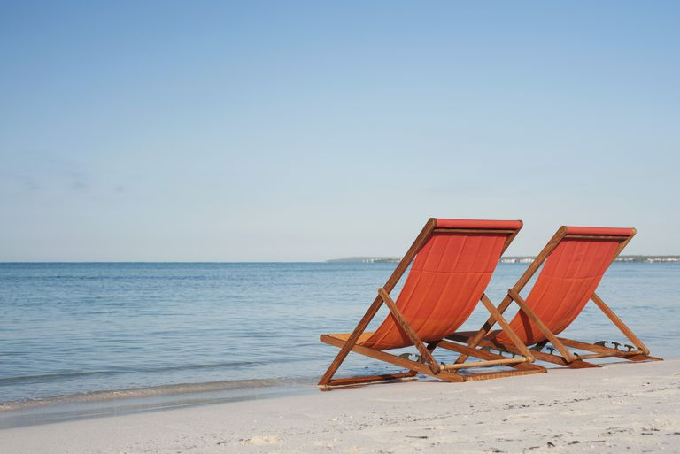 lounge chairs sitting at the surf line on a beach
