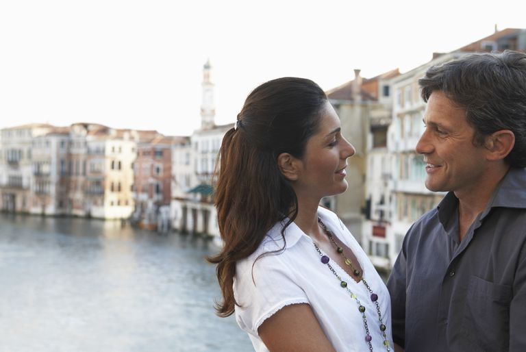 Couple embracing by canal, looking into each other's eyes