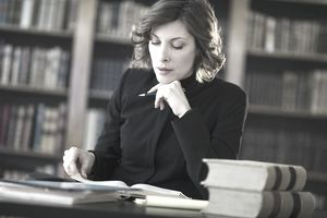 Legal professional studying in a library with books.
