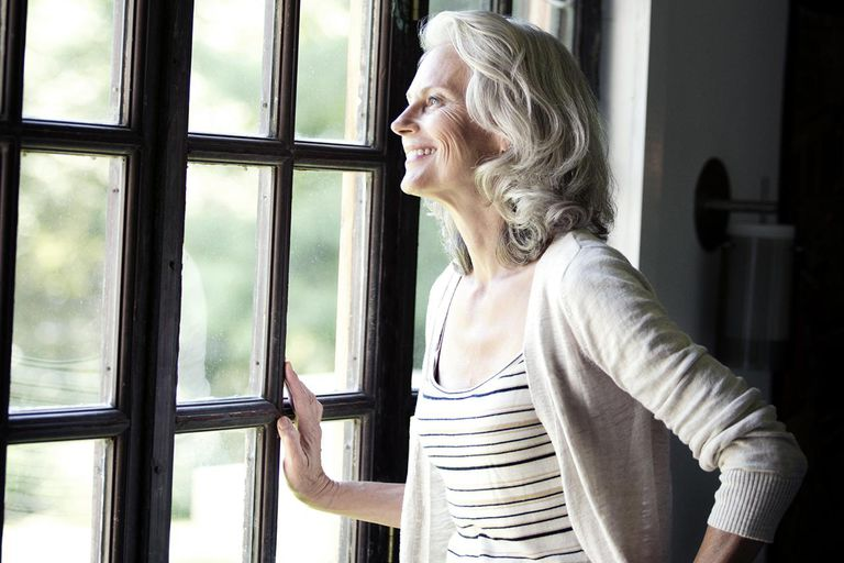 Senior Woman Smiling and Looking Out of Window