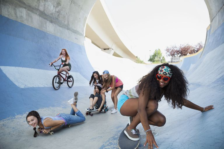 Teenage girls playing on skateboards at skateboard park