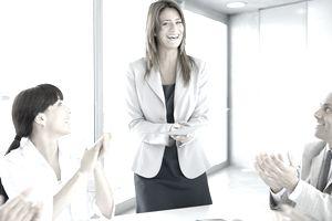 Business team applauding businesswoman