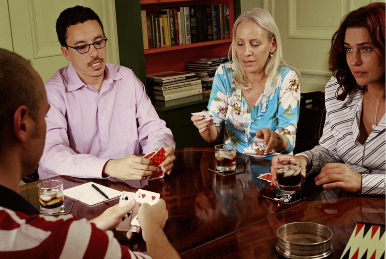 Friends playing cards at table