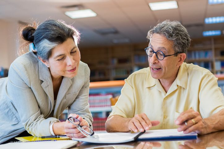 Teacher helping adult student in library