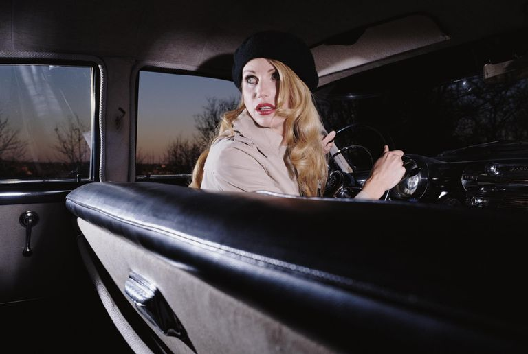 Frightened woman driving vintage car at dusk