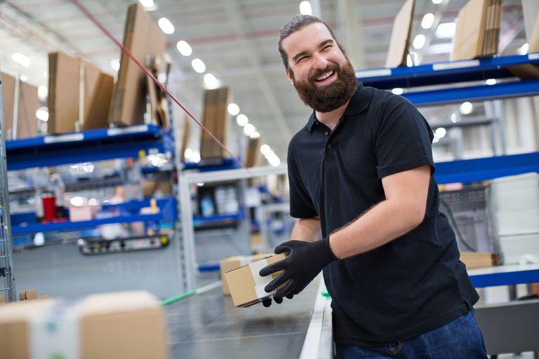 smiling man pulling product off conveyor belt