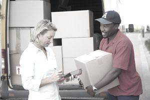 Delivery man holding cardboard box with customer