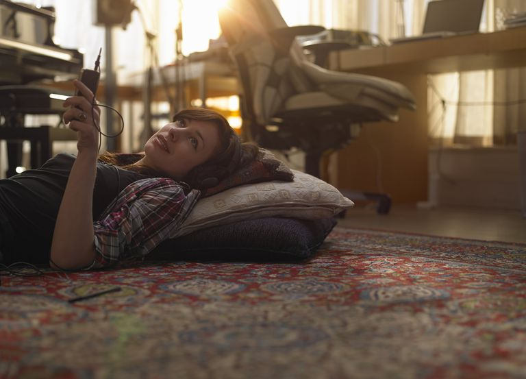 Woman relaxing on the floor with smartphone