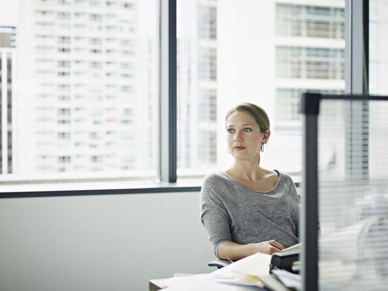 Businesswoman sitting at messy desk looking out