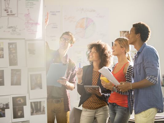 Four business people review qualitative and quantitative information.