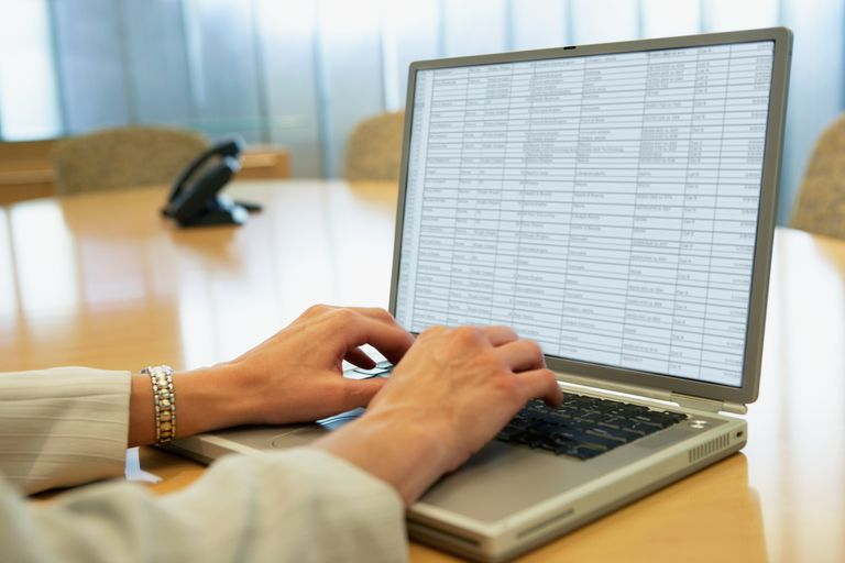Woman compiling spreadsheet on laptop