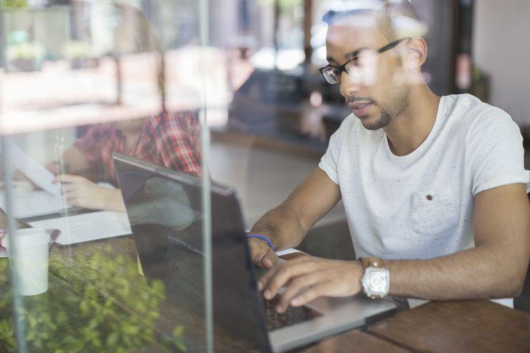 Man using laptop in cafe