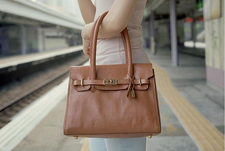 Young girl holding leather bag at train platform