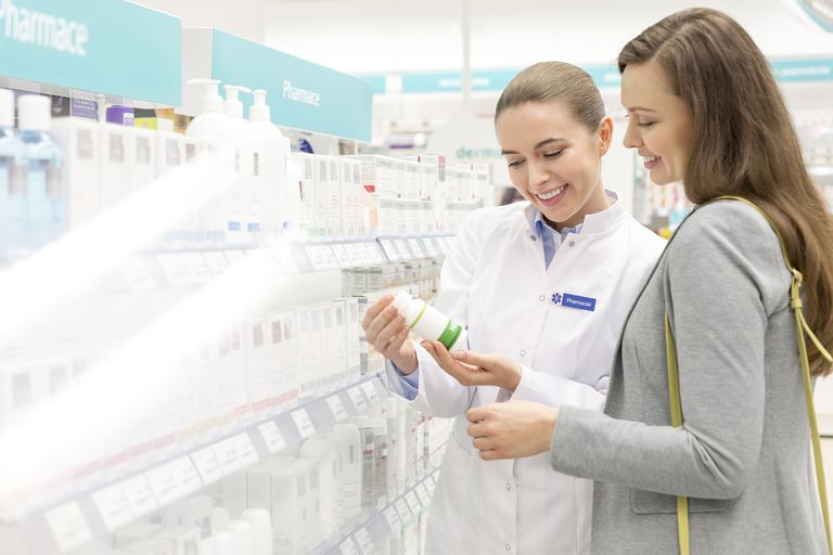 Pharmacist and customer reviewing label on bottle in pharmacy