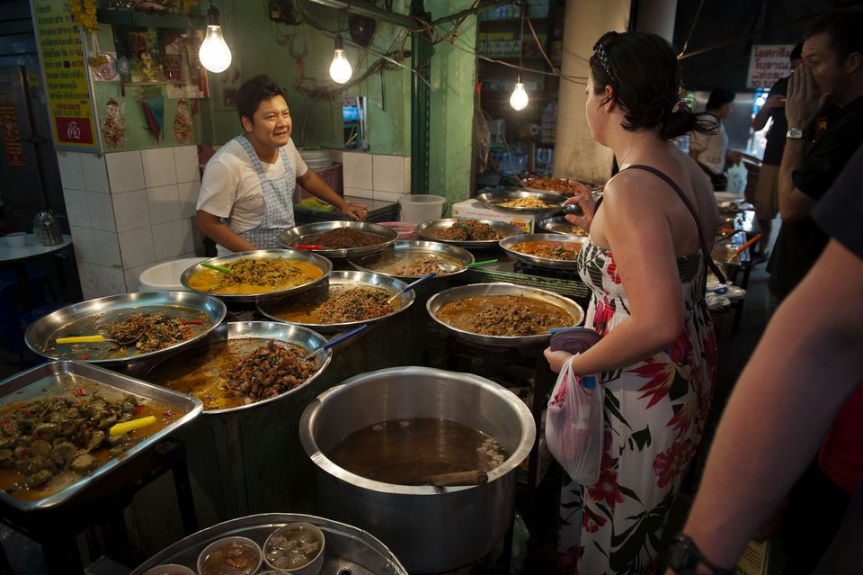 A female tourist ordering a selection of Thai food from a market vendor