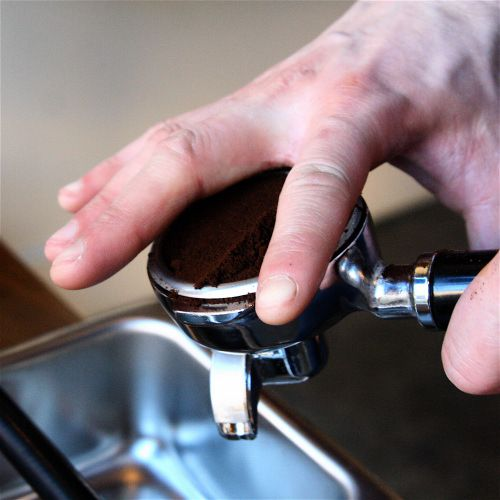 An image of a barista clearing updosed espresso grounds before tamping.