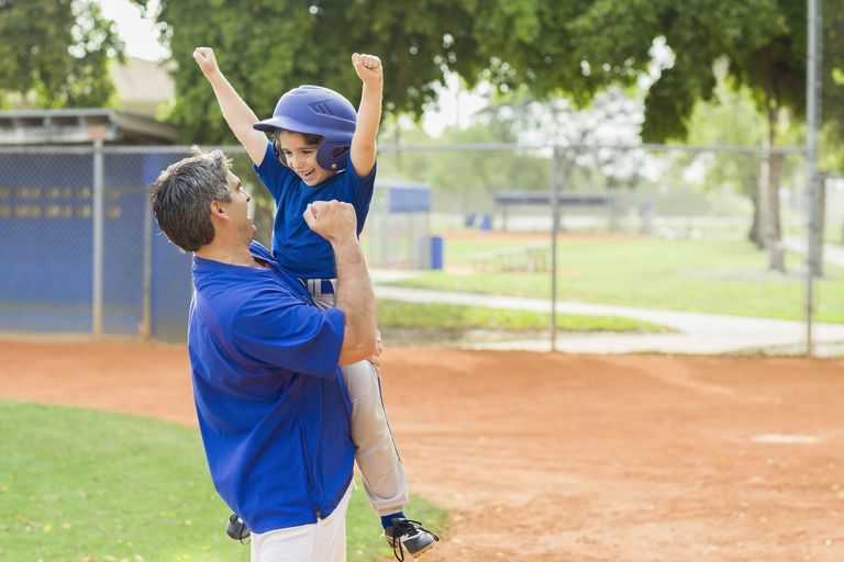 Good sports parent - dad and son celebrating at baseball game
