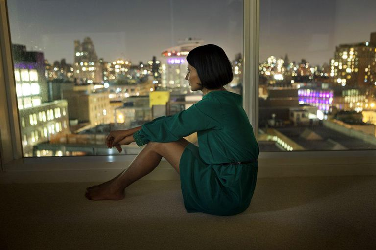 Woman looking out picture window at night