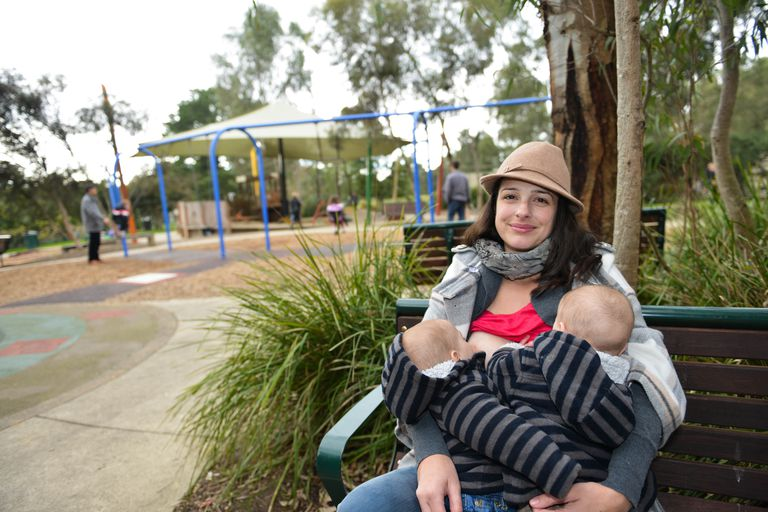 Mother breastfeeding twins at the park