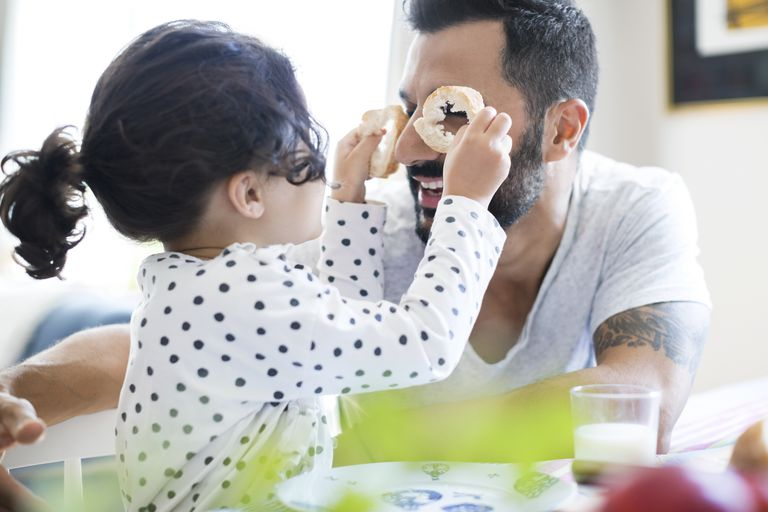 Single dad playing with his daughter at dinner