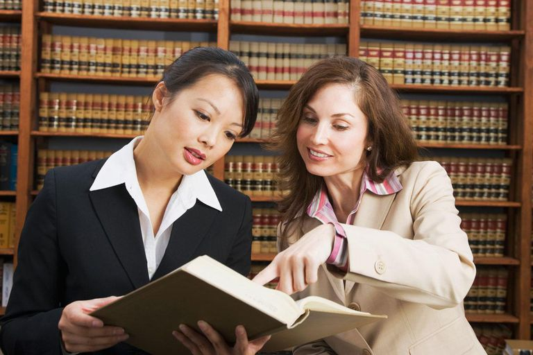 Multi-ethnic women looking at library reference book
