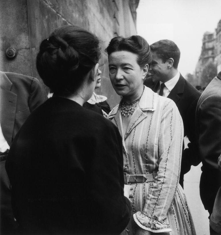 Simone de Beauvoir habla con Georges Arnaud (de espaldas), Paris, Francia.