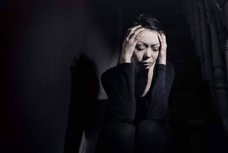 Woman in a dark room holding her head in pain