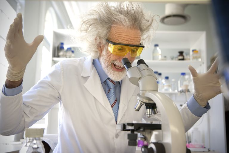 Tousled professor examining samples under microscope, looking surprised