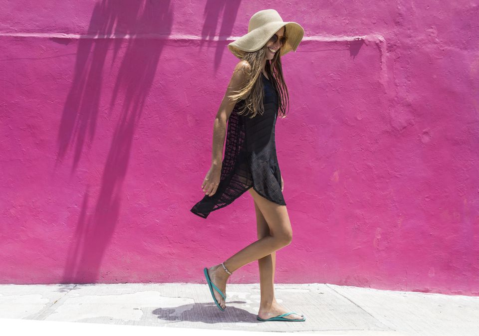 Woman with sun hat walking against bright wall