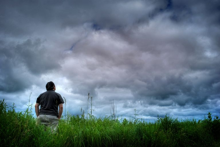 Man looking up stormy sky