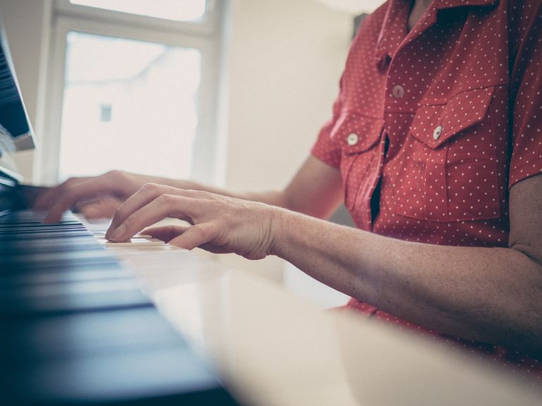 Cropped Image Of Young Woman Playing Piano At Home