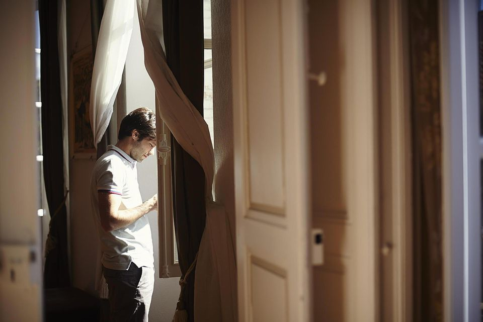 Mid adult man at apartment window using mobile phone