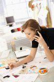 A fashion designer works on some designs at her desk.