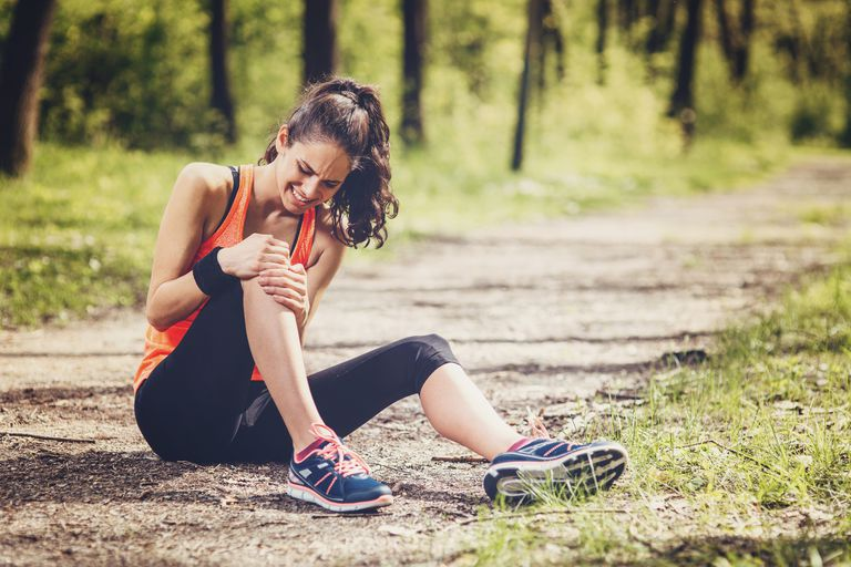 Young woman feeling pain in her knee