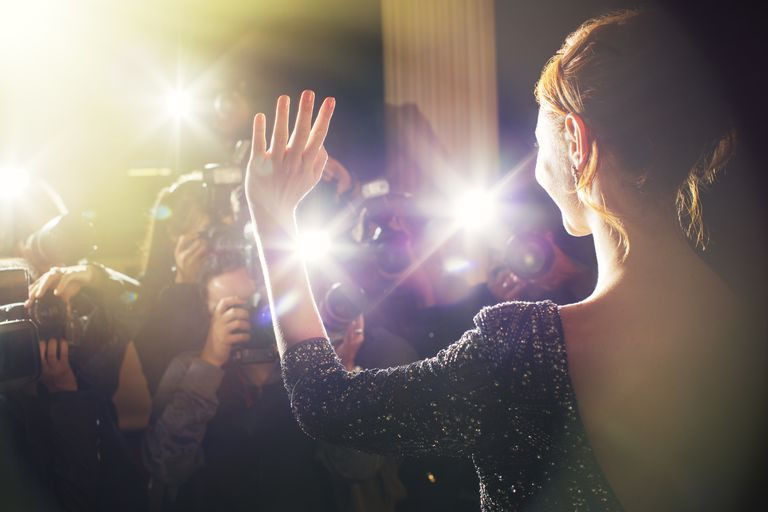 Celebrity waving for paparazzi photographers at event