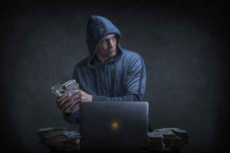 Photo of a man stealing cash next to a laptop computer