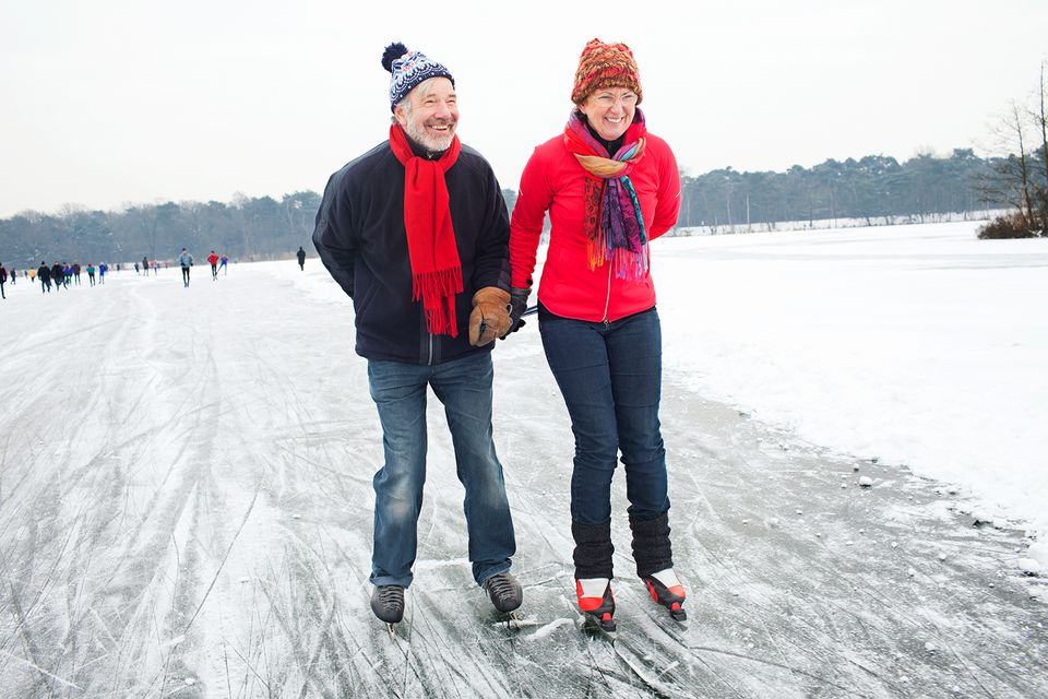 Couple holding hands while ice skating.